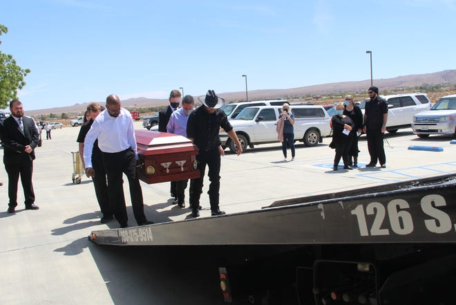 Pallbearers Ben Calvon, Carlos Herrera, Keith Simonet, Zedekiah Weaver, Kyle Lewis and Kevin LaBrie load the casket onto the tow truck Saturday after the service.