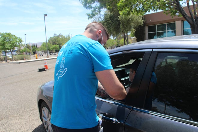 A healthcare worker administers a COVID-19 vaccination Saturday in front of City Hall in Ridgecrest.