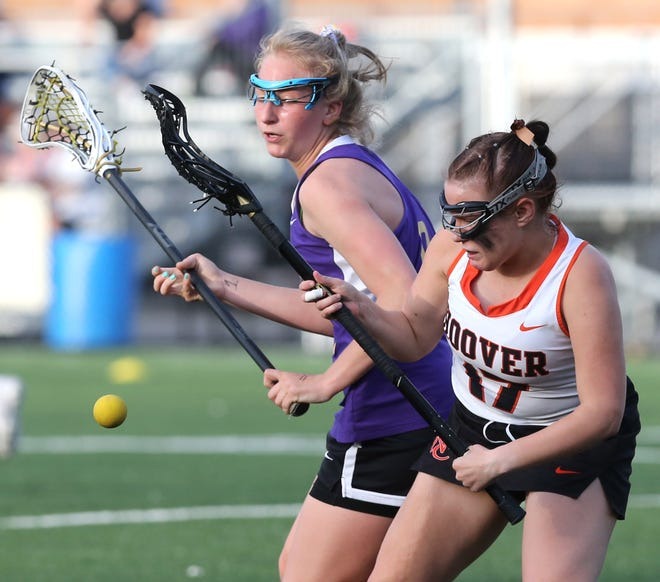 Jackson's Chelsea Debevec (left) fights for the ball with Hoover's Vivian Grover (17) during Tuesday's lacrosse game.