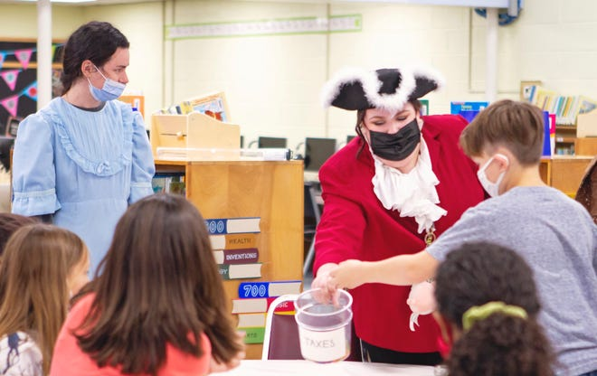 Monica Munroe (left) and Kasidee Norton (red jacket) teach the students about taxes during Colonial times.