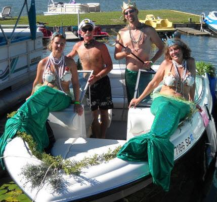 """Rain Kemperman, right, participates in a watercraft parade with her boat using a """"merfolk"""" theme."""