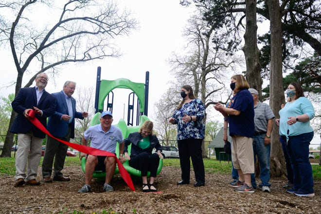 Choosing a nontraditional way to cut a ribbon Wednesday, Staci Wunder, recreation leader with the Parks and Recreation Department, and Bill Buscher, member of the Civitan Club of Topeka, slide down a new piece of playground equipment at the Civitan Day Camp facility inside Gage Park.