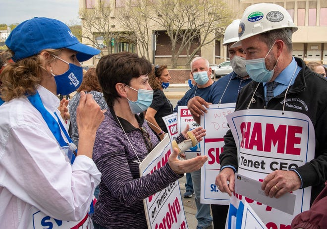 Nurses Marlena Pellegrino and Marie Ritacco, left to right, talk to Francis X. Callahan, president of the Massachusetts Building Trades Council, as Callahan arrives to deliver a letter to St. Vincent CEO Carolyn Jackson Wednesday.