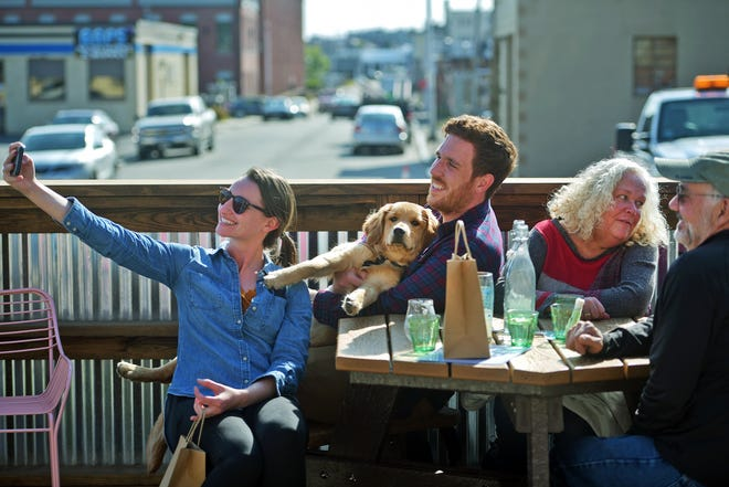 Katie and Luke Pukatch with their 9-month-old golden retriever, Winnie, take a selfie with Rose and Jim Hayes at Redemption Rock Brewing Co. Wednesday.