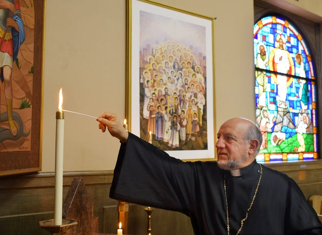 The Rev. Aved Terzian of the Armenian Church of Our Saviour in Worcester lights a candle Wednesday for the victims of the Armenian genocide depicted in the artwork behind him. He lights candles and prays daily to St. George and for the genocide victims.