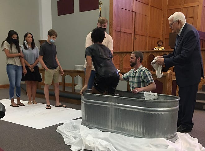 Kevin Asbury, youth minister at Christ Central Church in Rainbow City, uses a livestock water trough to baptize young church members who requested immersion baptism. (Christ Central is a Methodist congregation, a denomination where sprinkling usually is used for baptism). Pastor Billy York looks on.