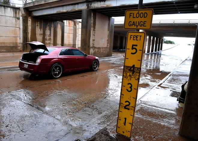 A flood gauge beside the northbound side of the Mockingbird Lane underpass indicates the height of the water that flooded the sedan behind it during thunderstorms early Wednesday. Heavy rains fell in Abilene throughout the morning hours, causing flooding in the city.