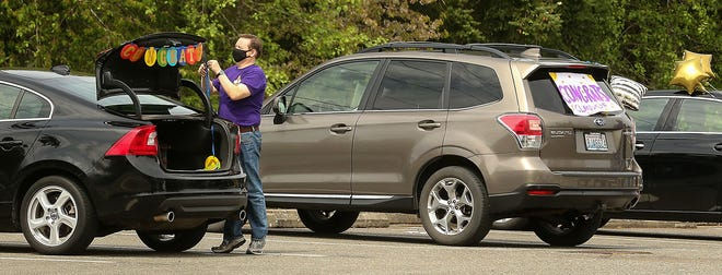 North Kitsap High School band teacher Bryce Adams decorates the trunk of his car as staff members prepare for a drive-thru event for seniors to pick up their graduation caps and gowns at North Kitsap High School in Poulsbo on April 28.