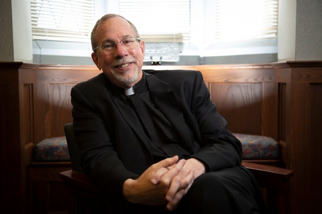 Rev. Michael Graham, outgoing university president, poses in an administration office at Xavier University in the Cincinnati neighborhood of Evanston on Monday, April 26, 2021. Graham is retiring from his position at Xavier after 21 years as president.