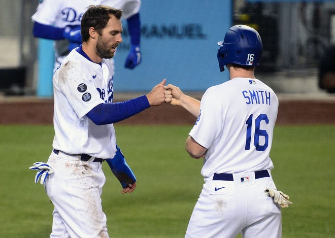 Los Angeles Dodgers left fielder Chris Taylor (3) and catcher Will Smith celebrate after both score runs against the Cincinnati Reds during the sixth inning at Dodger Stadium.