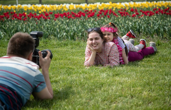 Vitaliy Grytsyk of Detroit, takes photos of his wife Anna and daughter Chaya, 5 next to a field of tulips at the Windmill Island Gardens in Holland on Tuesday, April 27, 2021.
