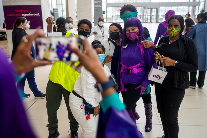 Medical workers take a group photos after receiving their monetary prizes distributed by Ally Bank in honor of National Superhero Day at TCF Center on April 28, 2021, in Detroit.
