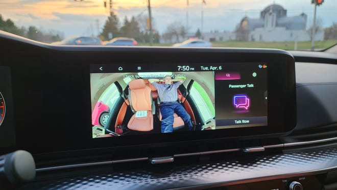 Detroit News auto critic Henry Payne reclines in the 2022 Kia Carnival's econd-row recliners. A console camera keeps an eye on him.