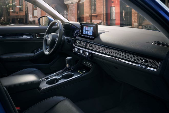 The simple interior of the 2022 Honda Civic sedan is anchored by a horizontal mesh that integrates air vents.