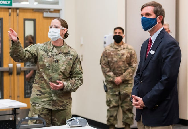 The Army 3rd Security Force Assistance Brigade's Stefanie Cocchimiglio, left, explains to Kentucky Governor Andy Beshear, right, the process of how COVID-19 vaccinations will be administered during the opening of a temporary federal vaccination clinic at the Henderson County Extension Office in Henderson, Ky., Wednesday afternoon, April 28, 2021.