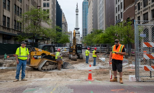 Workers wait for traffic to pass as construction on Market Street near the City Market on Wednesday, April 28, 2021.