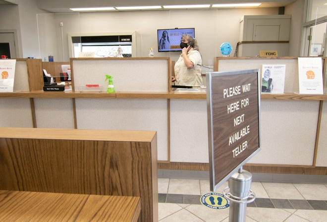 """Janet Nimke, a teller at Eaton Community Bank in Gregory, works with a customer via phone Wednesday, April 28, 2021. The bank branch will close in the end of July. Nimke, who grew up in Gregory, says of the closure """"It's hard, really hard. The bank's always been here."""""""