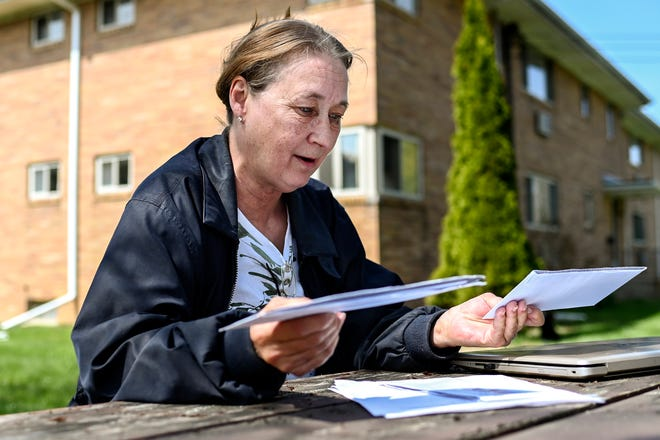 Lynda Thornburg sifts through the paperwork she's sent and received while dealing with a fraudulent unemployment benefits claim on Friday, April 23, 2021, outside her home in Lansing. Someone stole her identity and claimed benefits fraudulently using her name.