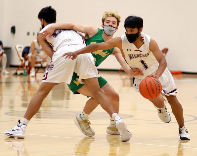 Senior Wildcat Jordan Caballero (1) worked off a screen by teammate Sebastian Villezcas on a drive to the basket. Caballero led the 'Cats with 13 points and also dished 5 assists and made 3 steals in a 58-40 loss to the Mayfield high Trojans on Tuesday.