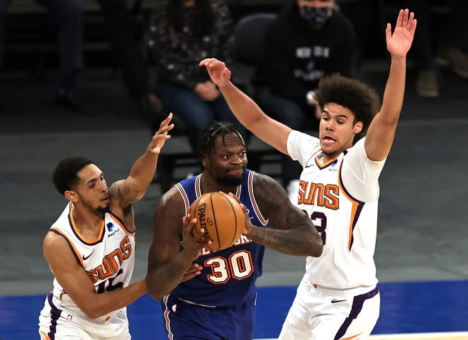 New York Knicks' Julius Randle (30) looks to pass as Phoenix Suns' Cameron Payne (15) and Cameron Johnson (23) defend in the first half of an NBA basketball game Monday, April 26, 2021, in New York. (Elsa/Pool Photo via AP).