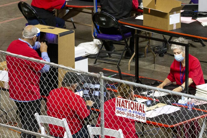 Maricopa County ballots from the 2020 general election are examined by contractors hired by the Arizona Senate at the Veterans Memorial Coliseum in Phoenix on April 27, 2021.