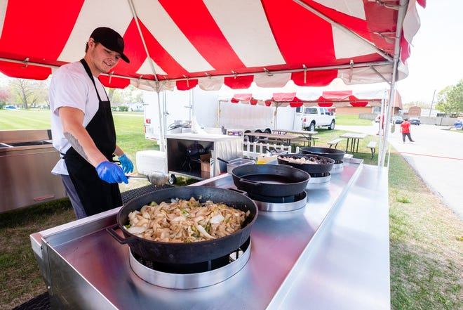 Austin Reno cooks onions and peppers in an iron skillet Wednesday, April 28, 2021, at House Of Flavour. House Of Flavour will be outside Silver Pines Apartments for the next several days.