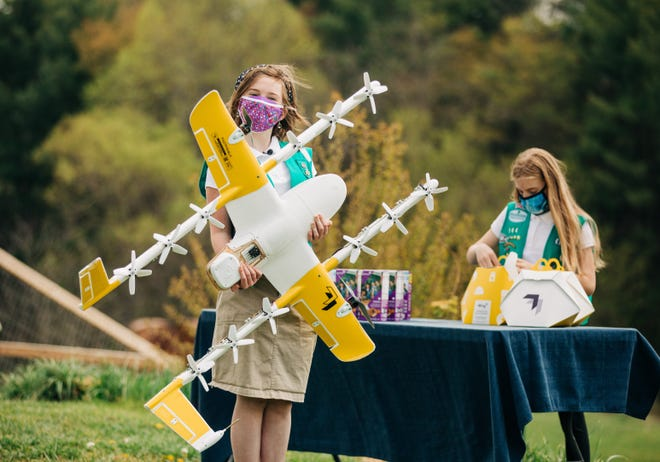 Girl Scouts Gracie Walker and Alice Goerlich help prepare orders with Wing for drone cookie deliveries in Christiansburg, Virginia.