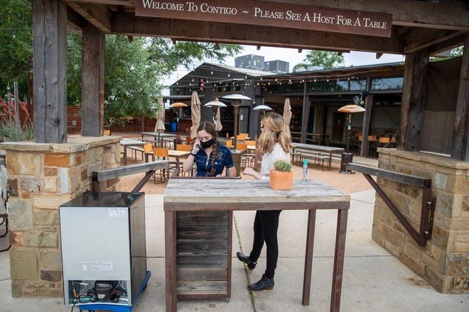 Contigo employees Katherine Curley and Chloe Fisher get ready to check in customers at the restaurant on April 27. The restaurant's outdoor seating is good for social distancing.