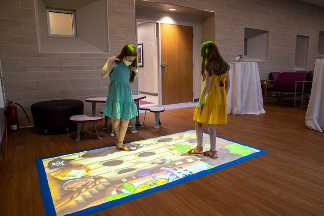 Eden Cessac, left, plays with her twin sister Noelle, 9, on Thursday while they wait for the beginning of the ribbing cutting ceremony at the new Dell Children's Specialty Pavilion. Different areas have computerized floor mats to entertain kids.