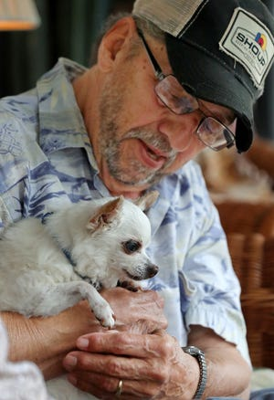 Bill Croft shares a moment with Brutus, his pet Chihuahua, at his Portage Lakes home. Bill and his wife, Katherine, rescued Brutus about 13 years ago.