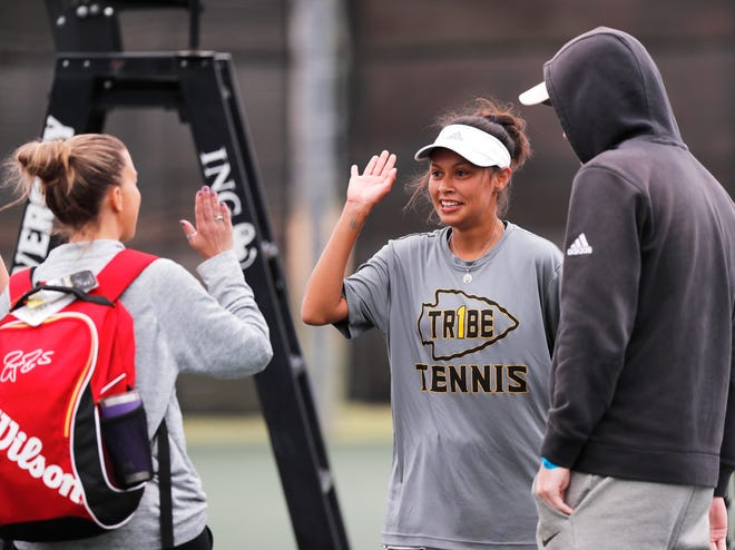 Seminole senior Marcela Guevara high-fives assistant coach Jamie Armstrong after Guevara and Lauren Smith won the girls doubles third-place match Thursday in the Region I-4A tournament at the McLeod Tennis Center.