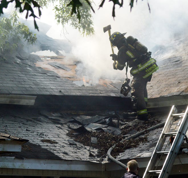 A firefighter cuts a vent for attic flames at the Campground Road fire.