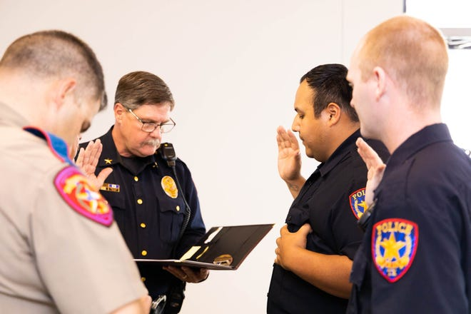 Early Police Chief David Mercer administers the Law Enforcement Oath of Honor to new officers Fidel Olalde (center) and Marvin Simpson during the Early City Council meeting Tuesday, April 27, 2021. Also pictured in foreground is Texas Department of Public Safety trooper Duke Hoy. Police corporals Andres Contreras and Michelle Sheedy were also promoted to the rank of sergeant at the meeting.