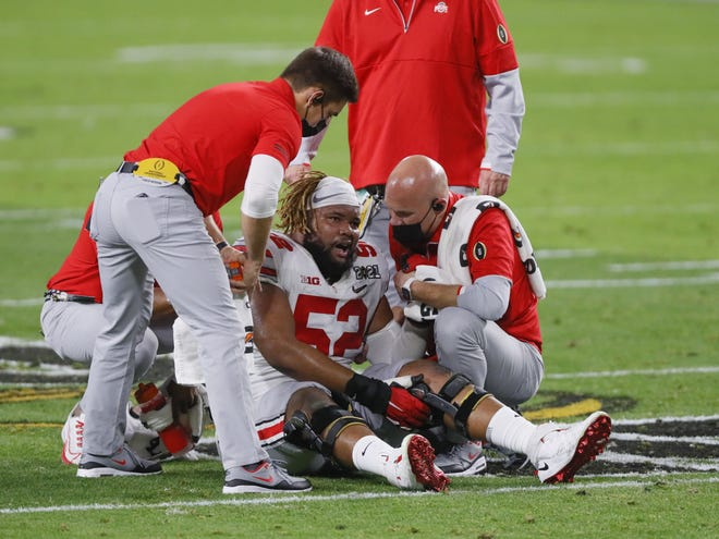 Wyatt Davis, here being tended to after aggravating a knee injury, was one of several Buckeyes missing or less than 100% in the CFP title game vs. Alabama.