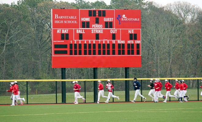 "The Barnstable High School Red Hawks baseball team runs around their new field with their new scoreboard at the end of their practice Thursday afternoon. Senior Casey Proto says, ""Getting back out there and finally being able to play on the field is really good."""