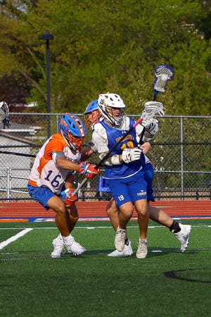 Penn Yan Academy's # 16 Tyler Griffin hits the stick of an Irondequoit player, forcing the ball to come out prior to his shot.