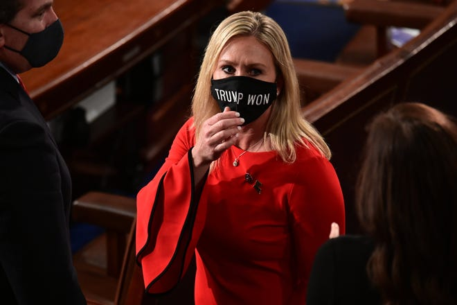 """Rep. Marjorie Taylor Greene, R-Ga., wears a """"Trump Won"""" face mask as she arrives on the floor of the House to take her oath of office on opening day of the 117th Congress at the U.S. Capitol in Washington, Sunday, Jan. 3, 2021."""