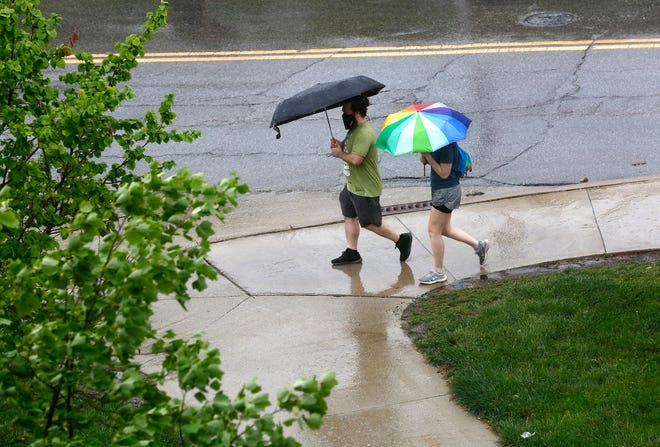 Two students walk in the rain towards the Ohio Union at The Ohio State University on Thursday. Rain hit the area again on Tuesday and was expected to continue later into the week.