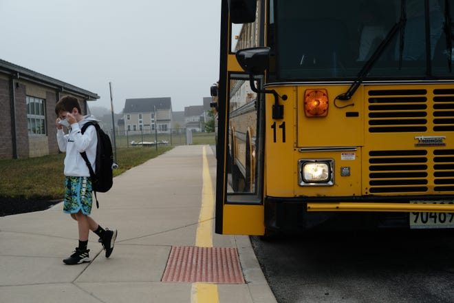 A student adjusts his mask as he steps the bus during first day of school on Sept. 1, 2020 at Heritage Elementary School in Lewis Center.