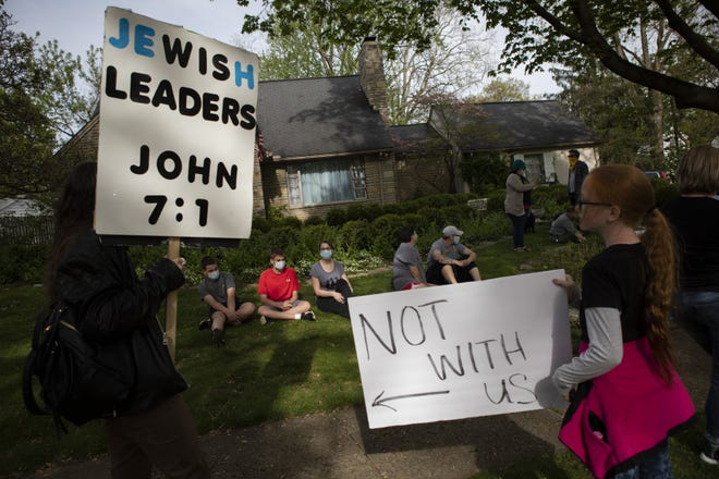 Shawn Kelly Jones, left, holds antisemitic signs on May 4 as the rest of a protest group attempts to distance themselves from him in front of the Bexley home of then-Director of the Ohio Department of Health Dr. Amy Acton. Antisemitic incidents in Ohio hit a 40-year high in 2020.