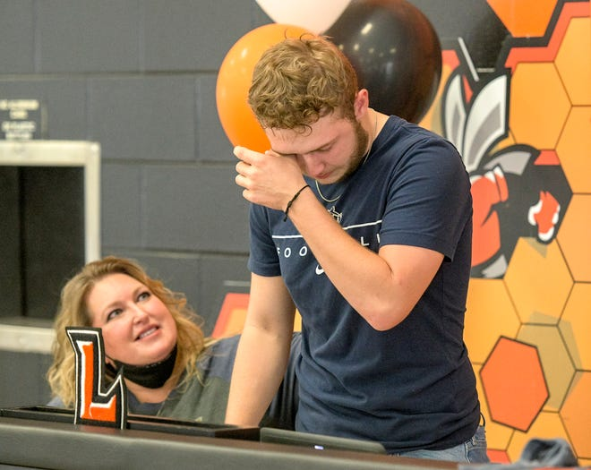 Devin McPherson is overcome with emotion during his signing ceremony Thursday at Leesburg High School. Sitting beside McPherson is his mother, Shannon. McPherson will attend North Carolina Wesleyan. [PAUL RYAN / CORRESPONDENT]