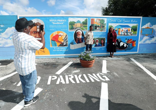 Rufus Pinkney Jr. and his sister, Sharon Pinkney, pose for a photo in September 2018 in front of the mural painted in memory of their late father, Rufus Pinkey Sr., who was a longtime shoe shiner and harmonica player.