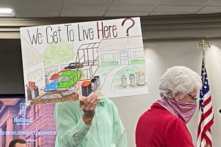 Holland resident Jim Schipper holds a sign opposing UDO, proposed changes to the city of Holland's zoning regulations, while his wife Linda speaks during a city council study session on Wednesday, April 28, 2021, in Holland, Mich.