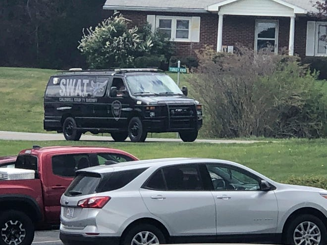 In this photo provided by WJZY, a tactical van from Caldwell County, North Carolina, sits on stand-by at a staging area in Boone April 28, 2021. Law enforcement agencies responded to a standoff in Boone in which two Watauga County sheriff's deputies were shot and wounded. (Morgan Frances/WJZY via AP)