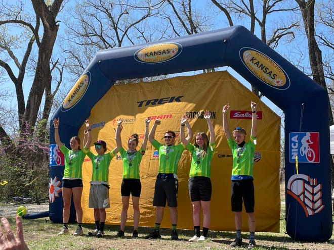 Members of the Hutch Composite mountain biking team celebrate after completing a race.