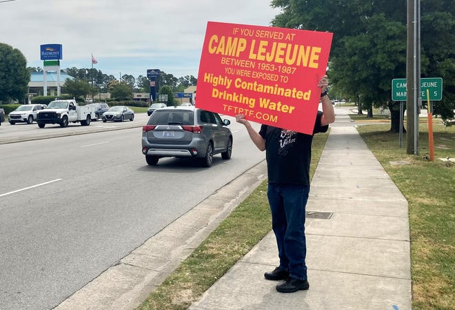 A Camp Lejeune veteran holds a sign as cars pass on Western Boulevard in Jacksonville during an outreach event organized by toxic water survivors, April 20, 2021 .