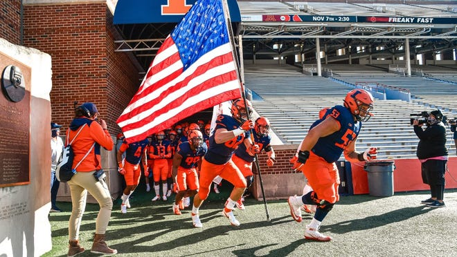 Peoria's Kendrick Green (53) leads the Illinois football team onto the field before a game against Purdue during the 2020 season.