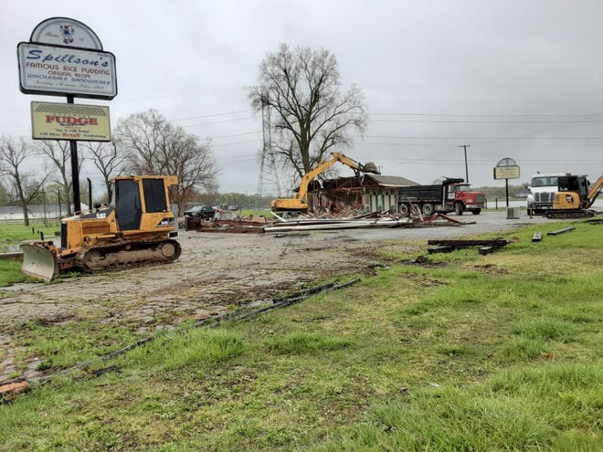 An excavator for Bush Contracting knocks down the building housing the former Spillson's Restaurant and Famous Original Rice Pudding and homemade fudge at the corner of N. Monroe St. (M-125) and N. Telegraph Rd. (US-24) Thursday afternoon in the rain.