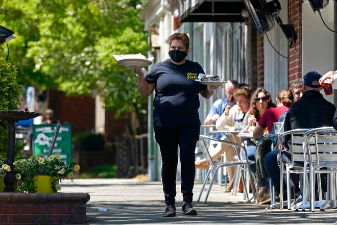 A member of the wait staff delivers food to outdoor diners along the sidewalk at the Mediterranean Deli restaurant in Chapel Hill, N.C., Friday, April 16, 2021.  The U.S. economy grew at a brisk 6.4% annual rate last quarter — a show of strength fueled by government aid and declining viral cases that could drive further gains as the nation rebounds with unusual speed from the pandemic recession.