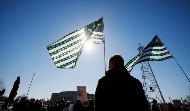 Julian Kerr of Oklahoma City holds a marijuana flag during a rally in 2020 to protest bills that would affect medical marijuana patients and businesses.